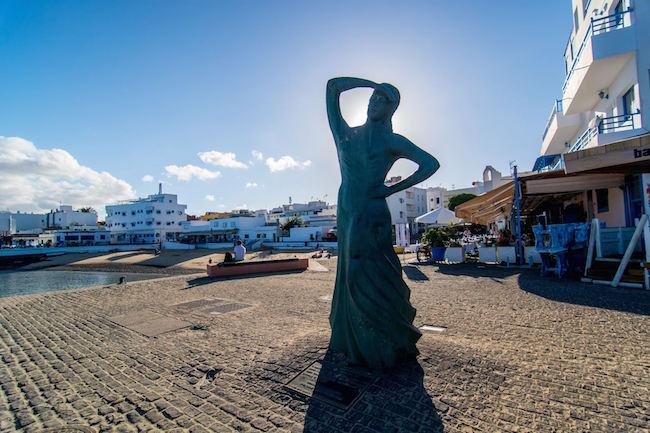 Een vrouw op uitkijk naar de vissersboten in Corralejo Viejo op het Spaanse eiland Fuerteventura