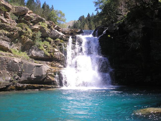 Een waterval die uitkomt in een helderblauw bergmeer in nationaal park Ordesa y Monte Perdido in de Pyreneeën van Aragon in Noord Spanje