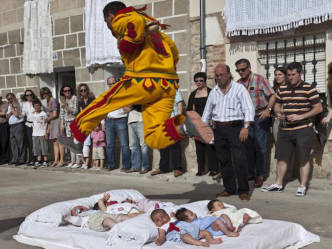 Een duivel springt over baby's heen tijdens het El Colacho feest in Castrillo de Murcia (Midden Spanje)