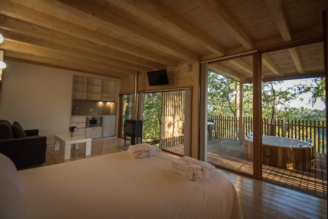 Deze boomhut in Galicië heeft een bed, zithoek, keukentje en kachel in een grote ruimte.