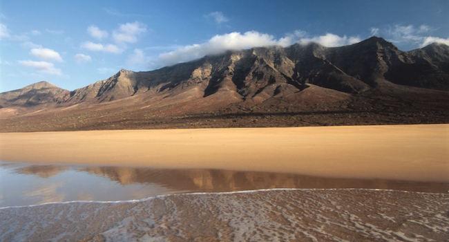 Kilometers lange fijne zandstranden met op de achtergrond het vulkanisch landschap van Canarische eiland Fuerteventura