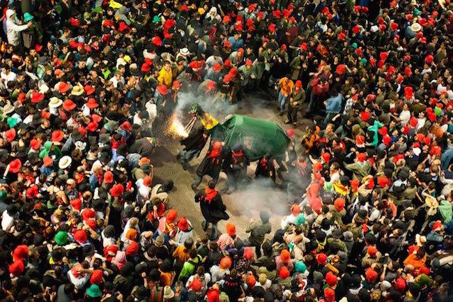 Een vuurspuwende draak omgeven door een mensenmenigte tijdens de Patum van Berga (Catalonië)