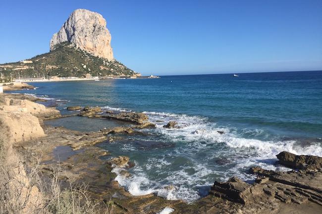 Verstopt in zee de Romeinse Baños de la Reina, met op de achtergrond de rots van Calpe