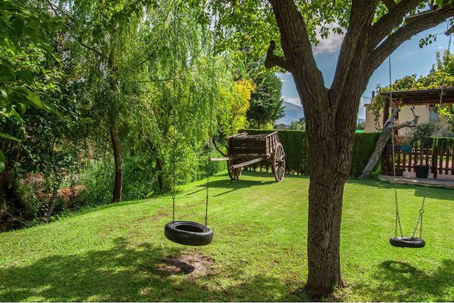 Grote groene tuin met zwembad en schommels van vakantiehuis Misqueres in Zuid Spanje