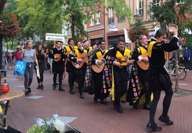 Muziekgroepen trekken zingend door de Nieuwstraat tijdens de Pasa calles van het Tuna Festival in Eindhoven