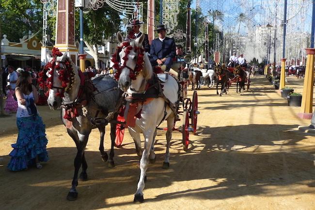Prachtig versierde paarden met paardenkoetsen tijdens de Feria del Caballo in Jerez